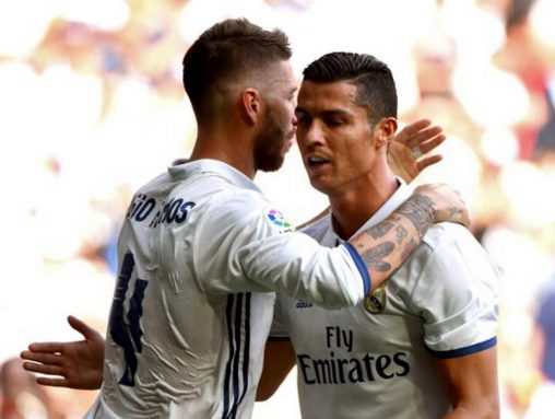Real Madrid's defender Sergio Ramos (L) is congratulated by Real Madrid's Portuguese forward Cristiano Ronaldo after scoring during the Spanish league football match Real Madrid CF vs CA Osasuna at the Santiago Bernabeu stadium in Madrid on September 10, 2016. / AFP PHOTO / GERARD JULIEN
