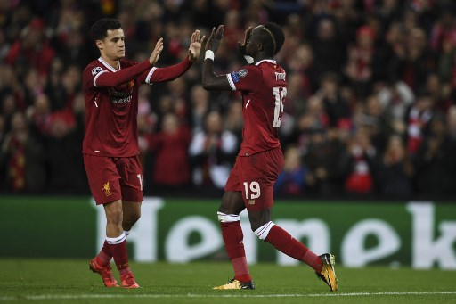 Liverpool's Senegalese midfielder Sadio Mane (R) celebrates scoring their sixth goal with Liverpool's Brazilian midfielder Philippe Coutinho (L) during the UEFA Champions League Group E football match between Liverpool and Spartak Moscow at Anfield in Liverpool, north-west England on December 6, 2017. / AFP PHOTO / Paul ELLIS