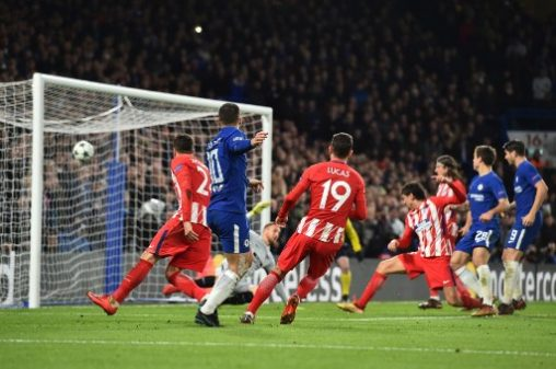 Chelsea's Belgian midfielder Eden Hazard (L) shoots goalward and Atletico Madrid's Montenegrin defender Stefan Savic (R) blocks to score an own goal during a UEFA Champions League Group C football match between Chelsea and Atletico Madrid at Stamford Bridge in London on December 5, 2017. / AFP PHOTO / Glyn KIRK