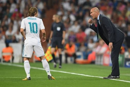 Real Madrid's coach from France Zinedine Zidane (R) gestures past Real Madrid's midfielder from Croatia Luka Modricduring the UEFA Champions League football match Real Madrid CF vs APOEL FC at the Santiago Bernabeu stadium in Madrid on September 13, 2017. / AFP PHOTO / GABRIEL BOUYS